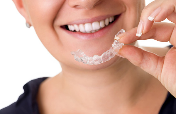 Woman with perfect teeth holding invisible braces